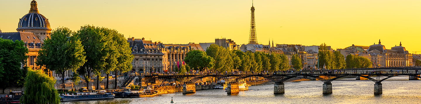 Learn French with Rosetta Stone. A cityscape of France with the sun gleaming on the buildings and water.