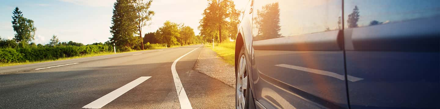 Car on the road header of Rosetta Stone Learn Spanish while Driving App page